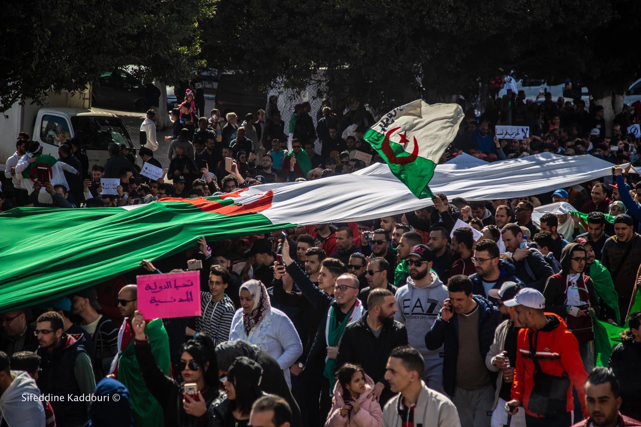 Tłum protestujących w Algierii trzyma nad głowami gigantyczną flagę tego kraju
